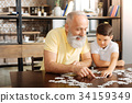 Happy grandfather doing jigsaw puzzle together 34159349