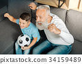 Little boy and his grandfather celebrating a goal 34159489