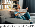 Grandfather increasing volume on TV set while 34159495