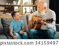 Loving grandfather playing guitar for his grandson 34159497