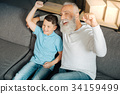 Little boy and his grandfather celebrating victory 34159499