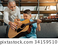 Loving grandfather and grandson having guitar 34159510