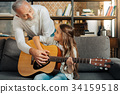 Loving grandfather teaching his granddaughter how 34159518