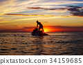 silhouette of a man on a jet ski in the sun 34159685