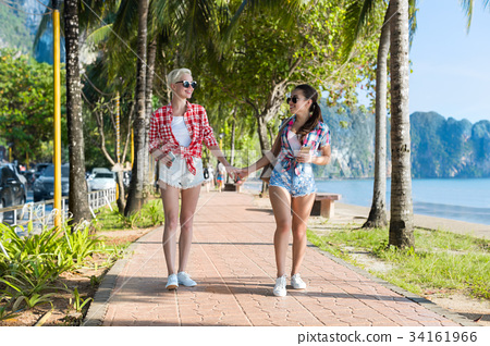 Two Woman Hold Hands Walking In Tropical Palm 34161966
