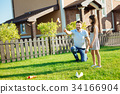 Happy father launching a paper plane in backyard 34166904