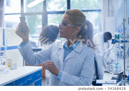 Female Scientist Examine Bottle With Chemicals 34168428