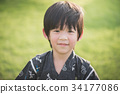 Asian boy in kimono with green field background 34177086