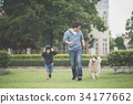 father and son walking with a siberian husky dog 34177662