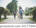father and son walking with a siberian husky dog 34177666