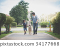father and son walking with a siberian husky dog 34177668