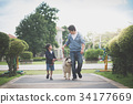 father and son walking with a siberian husky dog 34177669