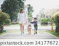 mother and son walking with a siberian husky dog 34177672
