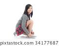 asian girl tying shoelaces on white background 34177687