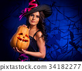 Halloween pumpkin in witch woman hands. 34182277