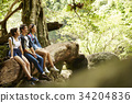 three young hikers are relaxing and sitting on a tree in forest 34204836