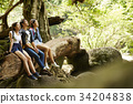 A group of three friends is enjoying the fresh air in the forest. 34204838