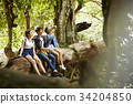 three young people are sitting and relaxing on the trunk to drink water. 34204850