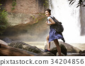 a young girl is standing near the waterfall and smiling. 34204856
