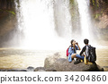 A couple is resting on the rock near the waterfall. 34204860