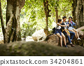 three young people are passing water bottle to drink in a forest. 34204861