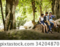 Three people are relaxing and chatting on a tree in the forest. 34204870