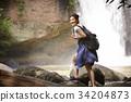 A happy traveler is walking on the rock near the waterfall. 34204873
