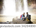A happy couple is sitting on the rock near the waterfall. 34204890