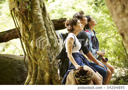 three people are taking a deep breath of fresh air in a forest. 34204895