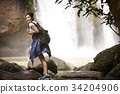 A young traveler is walking on the rock near the waterfall. 34204906