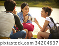 young travellers are drinking coffee and resting on the riverside 34204937