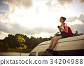 A girl is sitting on a rooftop of the van and enjoying views of the nature 34204988