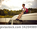 A girl is resting on the rooftop of the van near a river in the forest 34204989