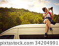 A girl is sitting on a top of a car, taking a photo of the nature by a digital camera 34204991