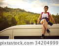 a beautiful girl is sitting on a rooftop of the van in the forest 34204999