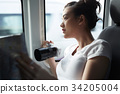 the girl is holding a camera and looking through the train window 34205004