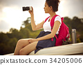 a young girl is sitting and taking photos with her digital camera outdoors 34205006