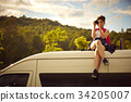 young girl is taking photos while sitting on a rooftop of the van 34205007