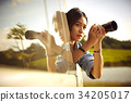 a young girl with digital camera is sitting in a truck and taking photos 34205017