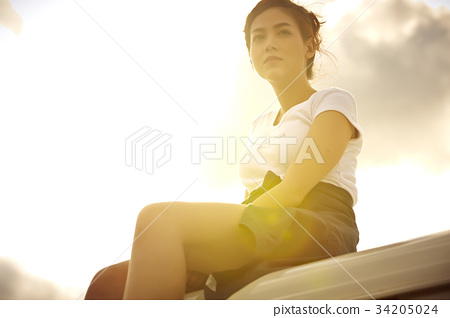 a young girl is sitting on truck's roof outdoors 34205024