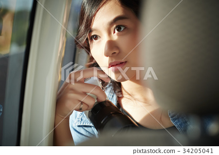 an asian girl with camera is looking outside from a truck 34205041