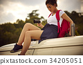 a young female traveler is sitting on a top of a car and holing digital camera 34205051