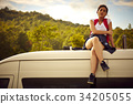 a young female traveler is sitting on truck's roof 34205055