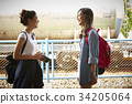 two happy young female travelers with camera are standing and talking 34205064