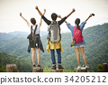 Three people are standing on the top of the moutain and enjoying the fresh air. 34205212