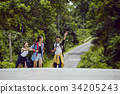 Three travellers are having fun and walking on the road 34205243