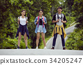 Three young traveller are standing on the road and smiling 34205247
