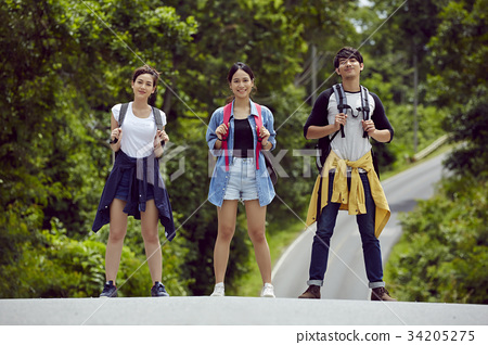 three travellers are standing on a road, smiling and posing 34205275