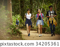 three asian persons are on the way to their destination in forest 34205361