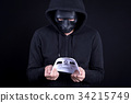 Mystery man holding and looking at white mask 34215749